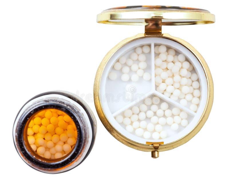 Compacte pillendoos en kruik met homeopathieballen stock foto