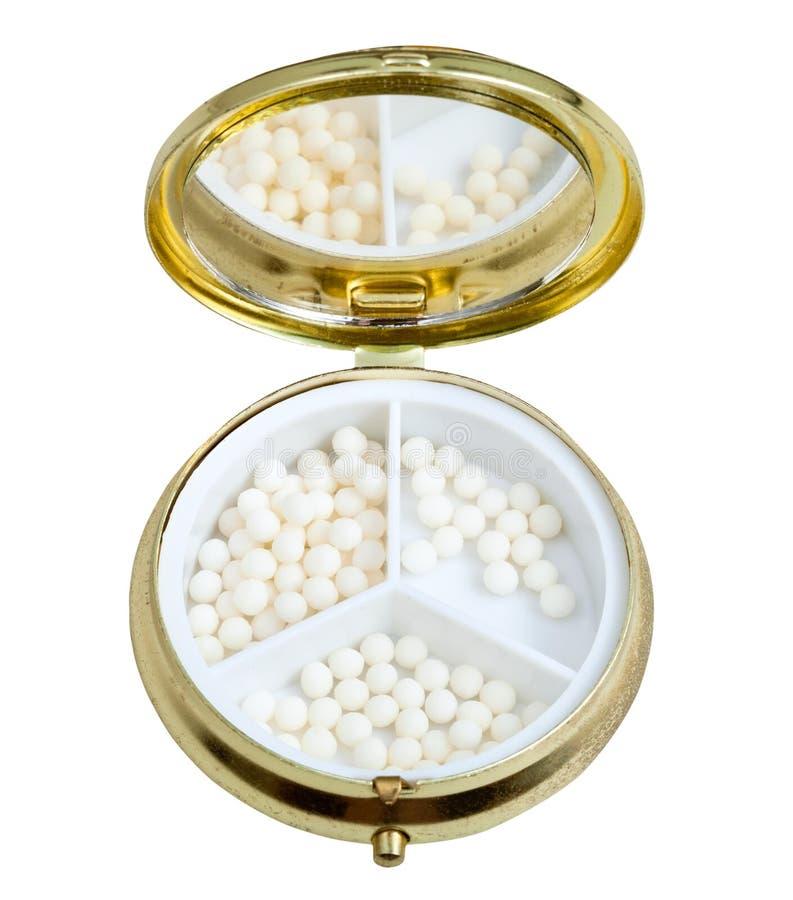 Compacte pillendoos met spiegel en homeopathieballen stock afbeelding