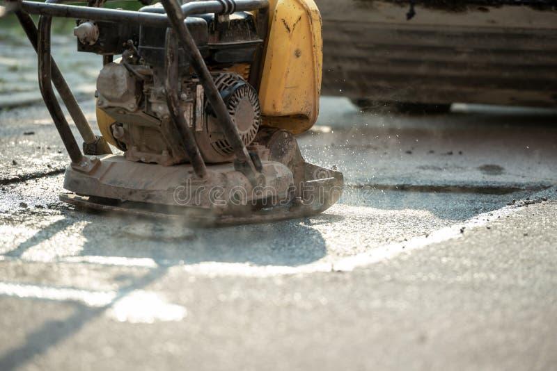 Compacteur finissant la dernière phase d'étendre le nouvel asphalte photos stock