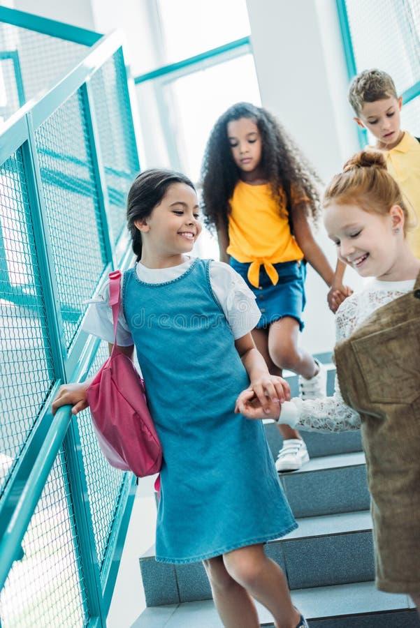 compagni di classe adorabili felici che camminano giù le scale fotografia stock