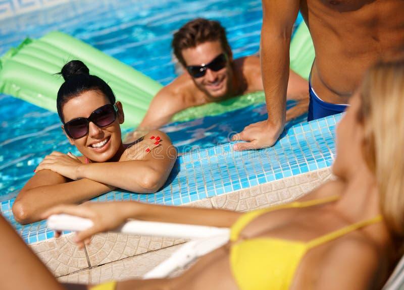 Compagnia felice nella piscina fotografia stock