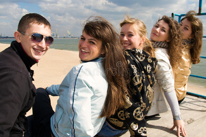 Compagnie des cinq jeunes s'asseyant ensemble photo libre de droits