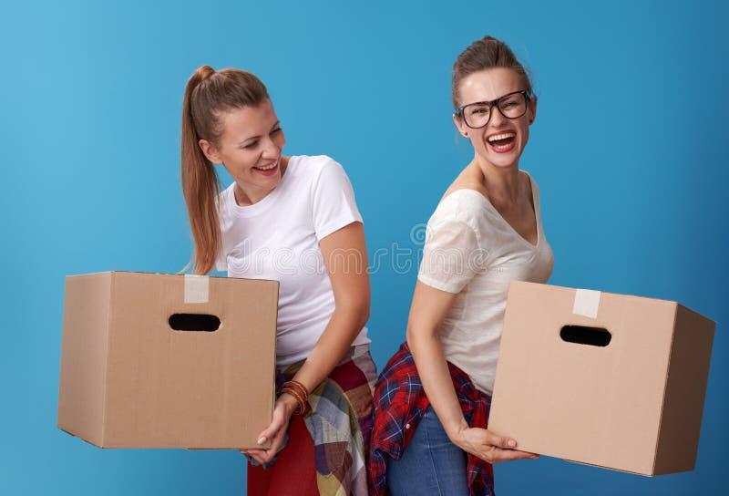 Compagnons de chambre actifs heureux de hippie tenant des boîtes en carton sur le bleu photographie stock