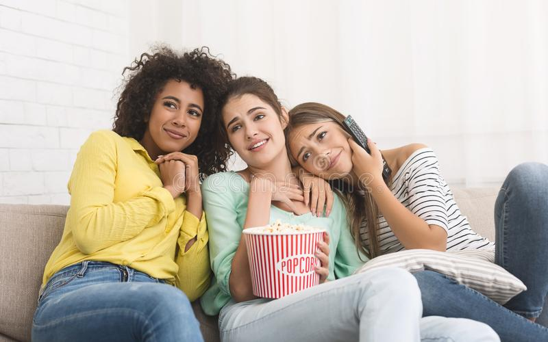 Companheiros de quarto que olham o filme com emo??o macia em casa imagem de stock