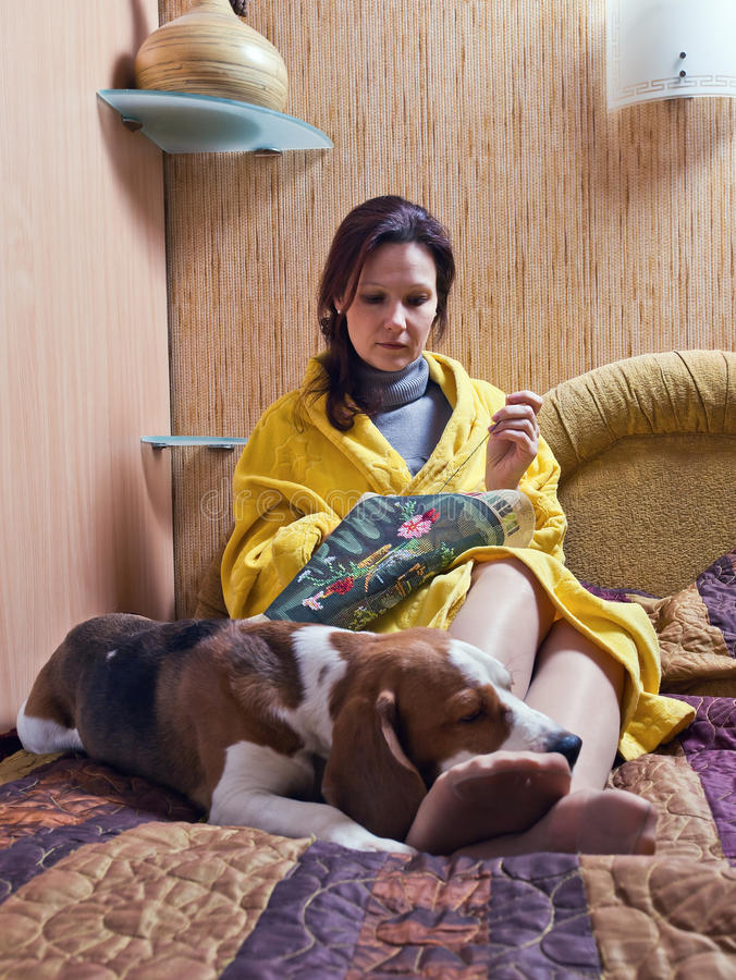Companion. The woman of middle age with a dog in a bedroom stock photo