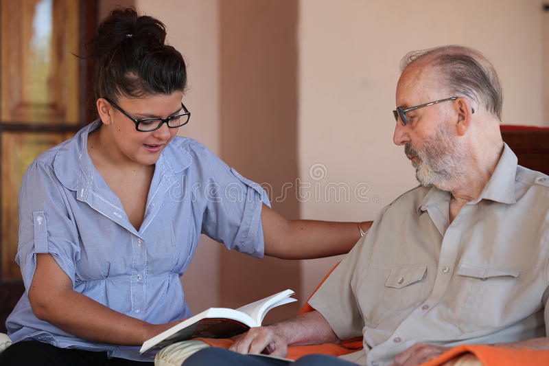 Companion or granchild reading to senior or grandfather. Companion or granchild reading to elderly senior or grandfather stock photos