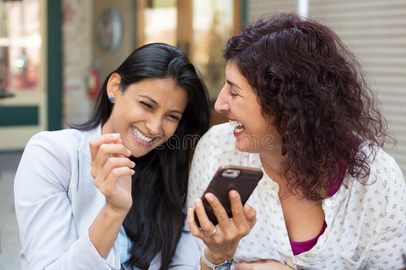 Companions laughing at texts stock photography