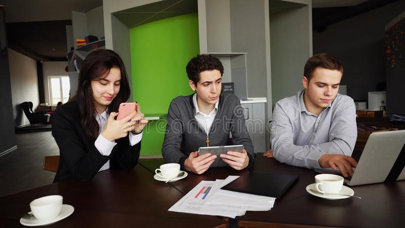 Three busy company employees, two young men and woman busy with stock images