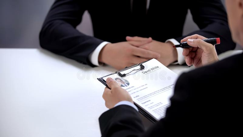 Company CEO holding curriculum vitae of employer, making decision, employment. Stock photo stock image