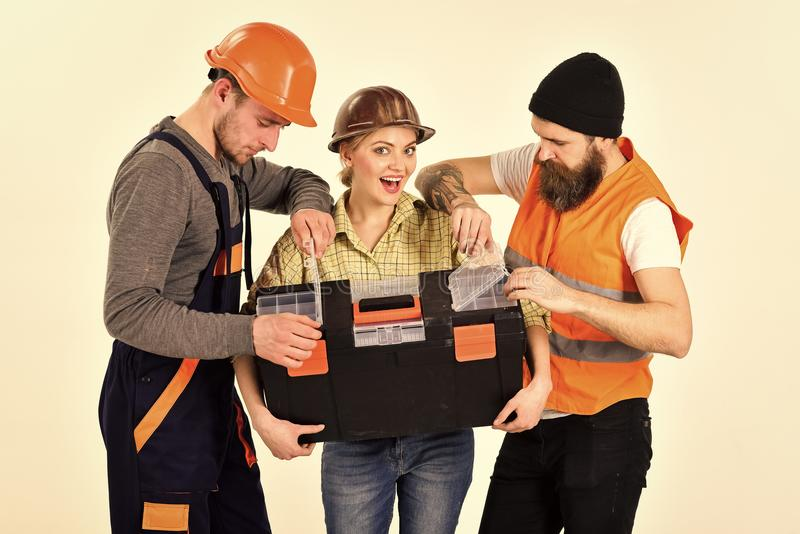 Company of cheerful workers, builder, repairer, plasterer. Strong woman concept. Woman holds toolbox, man looking in stock photo