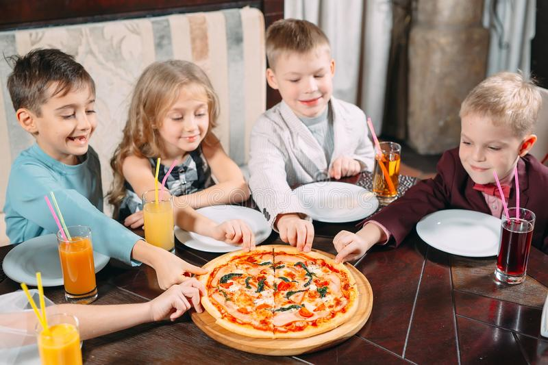 Company of children eat pizza in the restaurant royalty free stock images