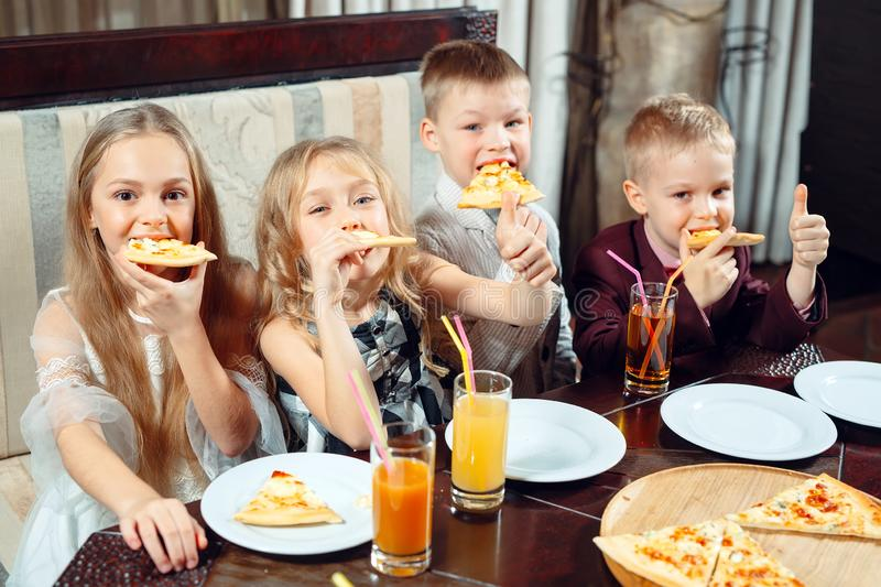 Company of children eat pizza in the restaurant. Children eat pizza in the restaurant royalty free stock photos