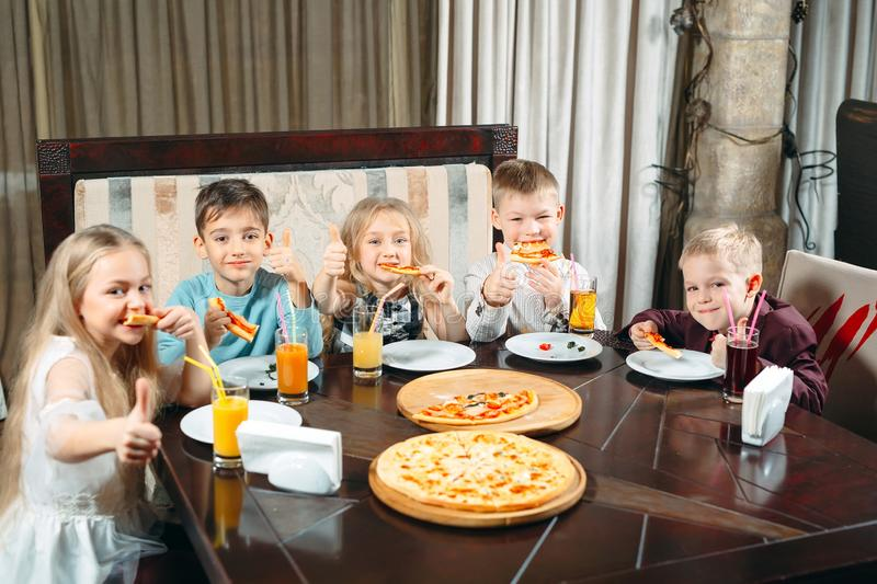 Company of children eat pizza in the restaurant. Children eat pizza in the restaurant stock image