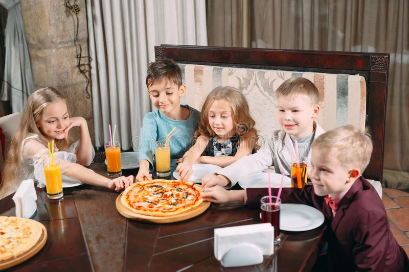 Company of children eat pizza in the restaurant. Children eat pizza in the restaurant stock photo