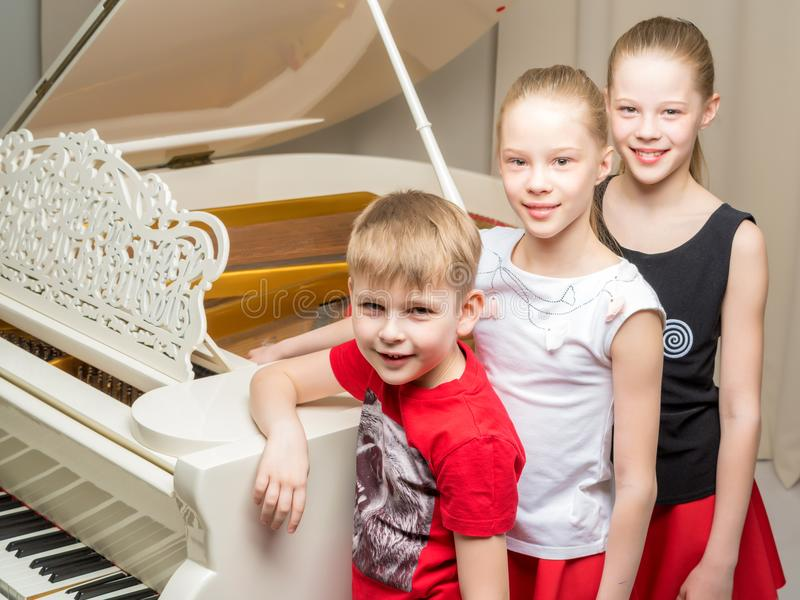 A company of children near the white piano. A cheerful company of children near a white grand piano. The concept of music education, children`s holidays royalty free stock photo