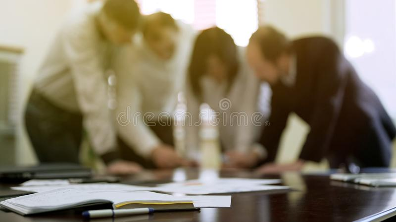 Company colleagues discussing report papers at business meeting, cooperation royalty free stock photography