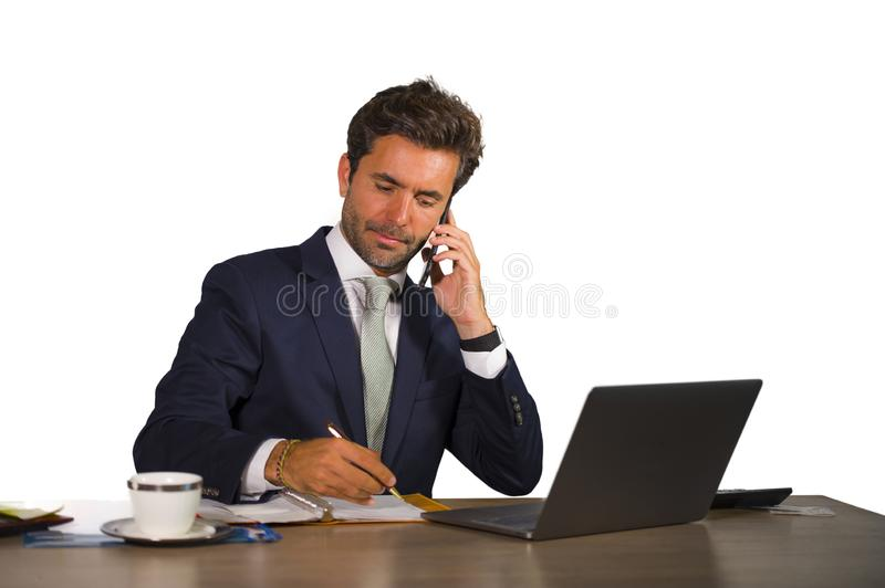 Company corporate isolated portrait of young handsome and attractive businessman working at office desk talking on mobile phone co royalty free stock photos