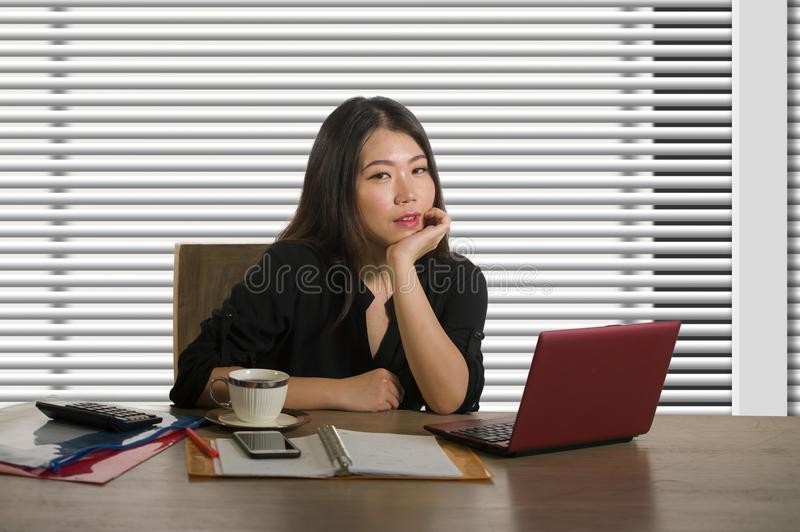 Company corporate portrait of young beautiful and busy Asian Chinese woman working busy at modern office computer desk by venetian stock photo
