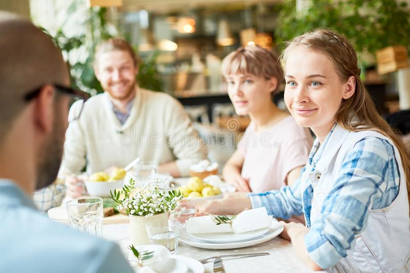 Company of friends conversing in cafe stock image