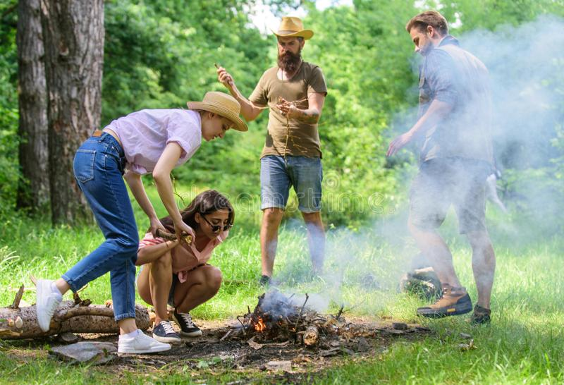 Company friends or family making bonfire in forest nature background. Friends working as team to keep bonfire. Add some. Wood to fire. Company camping forest stock photos