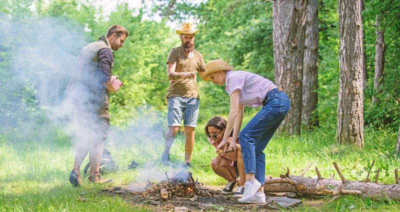 Company friends or family making bonfire in forest nature background. Friends working as team to keep bonfire. Company. Camping forest prepare bonfire for stock images