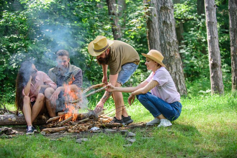 Company friends or family making bonfire in forest nature background. Company youth camping forest prepare bonfire for. Picnic. Friends hang out near bonfire royalty free stock image