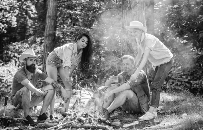 Company friends or family picnic roasting food. Plan for perfect day hike picnic. Friends relaxing near bonfire royalty free stock images