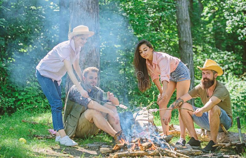 Company friends or family picnic roasting food. Plan for perfect day hike picnic. Friends relaxing near bonfire royalty free stock photos