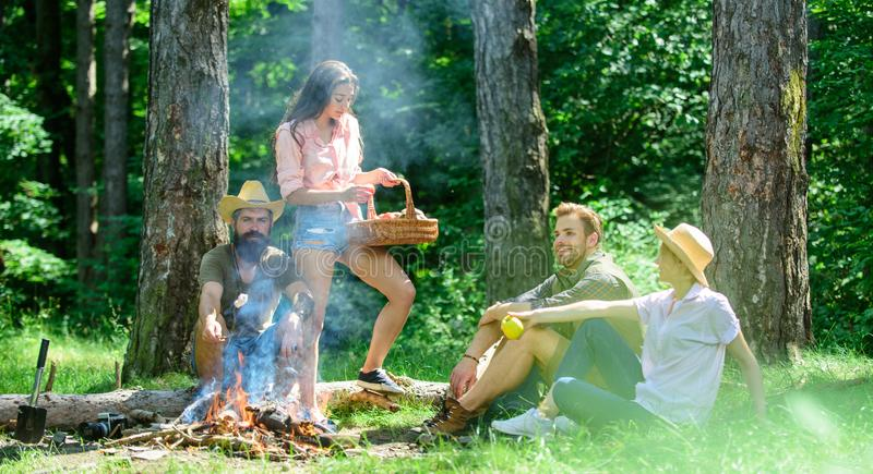 Company friends or family relaxing picnic. Friends relaxing near bonfire. Friends enjoy vacation or leisure nature. Forest background. Pleasant hike picnic in stock image