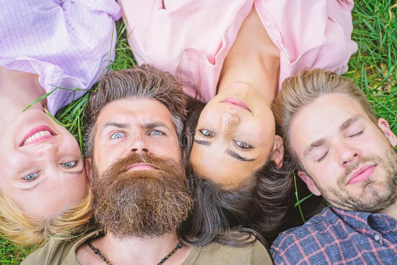 Company friends lay on grass top view. Diversity concept. They are different but best friends. Youth men and women lay. Close head to head. Tender blonde or royalty free stock photo