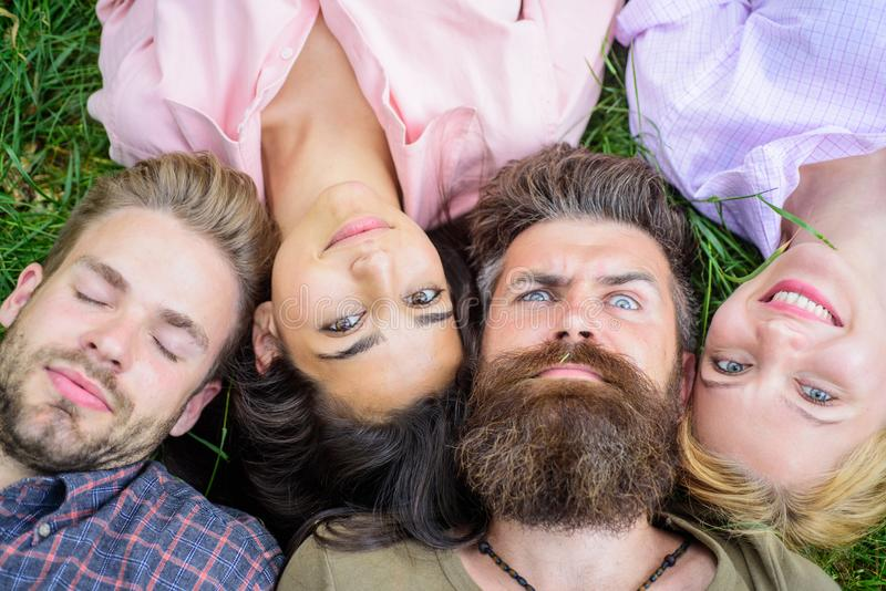 Company friends lay on grass top view. Diversity concept. They are different but best friends. Youth men and women lay. Close head to head. Tender blonde or stock images