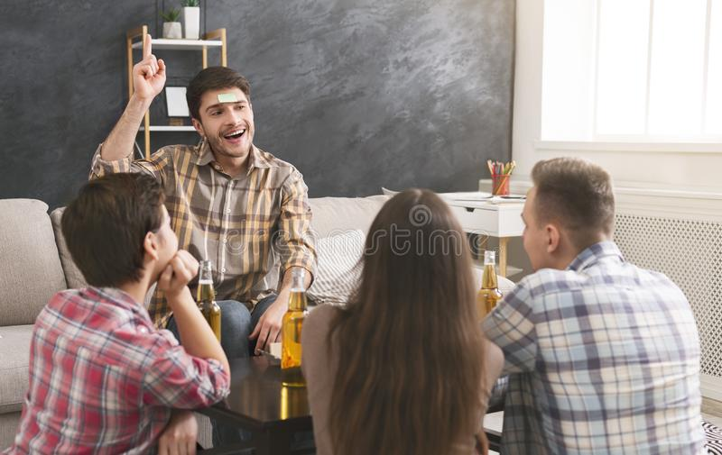 Company of friends playing forehead game at home stock images