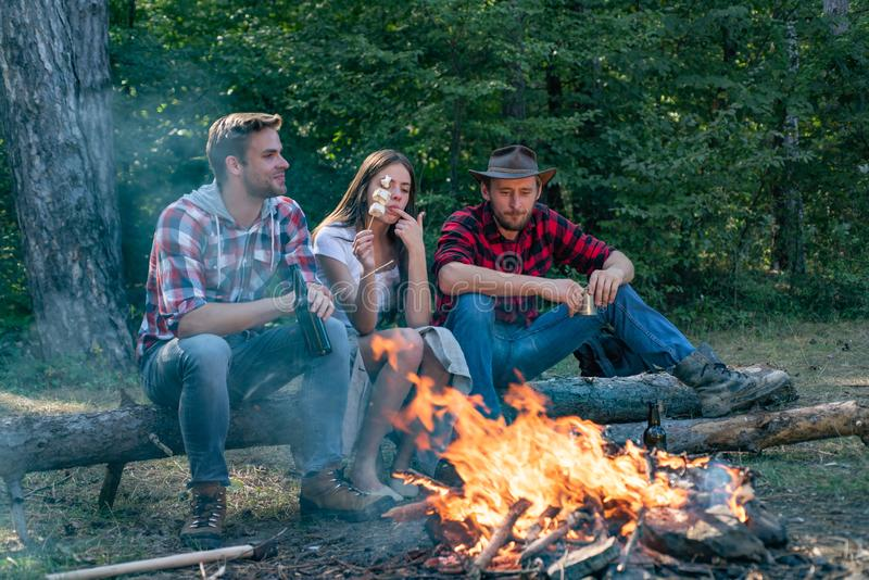 Company friends spend great time picnic or barbecue near bonfire. Picnic friends. Friends roasting hotdogs on sticks at stock images