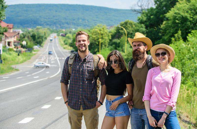 Company friends strats adventure with hitchhiking. Friends hitchhikers looking for transportation sunny day. Family. Weekend. Company friends travelers stock photos