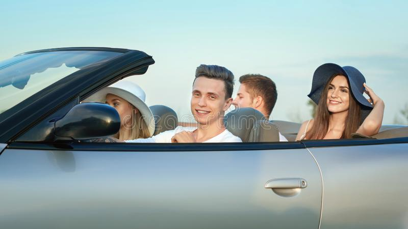 Company sitting in cabriolet, traveling by car. stock photos