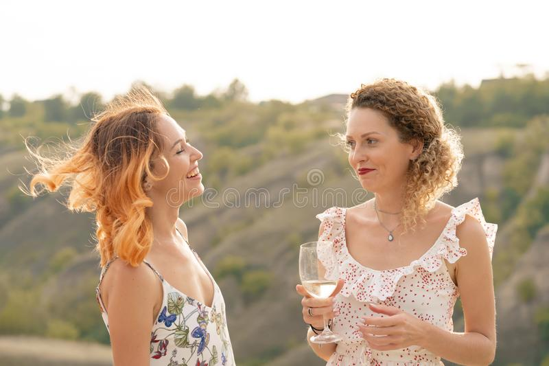The company of gorgeous female friends having fun, drink wine, and enjoy hills landscape picnic stock photos
