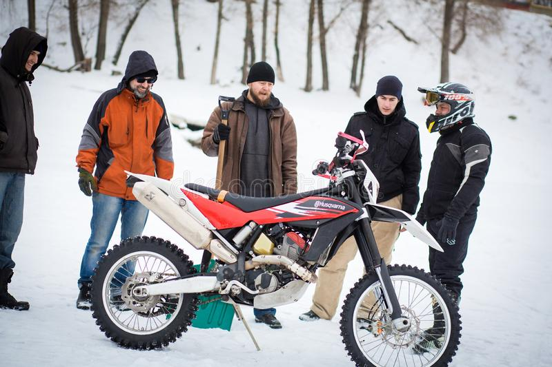 Company guys prepare motorcycle for ride on a frozen lake royalty free stock photo