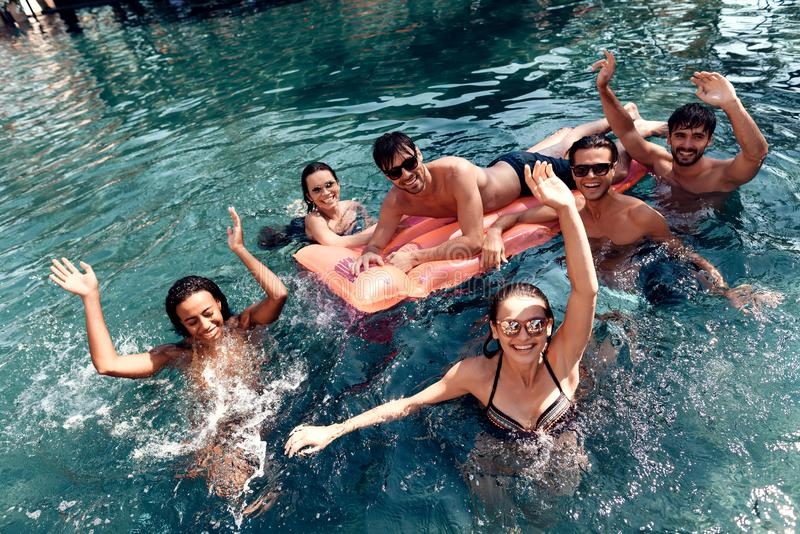Company of happy friends carefree spend time swimming in pool. Swimming pool party concept. royalty free stock images
