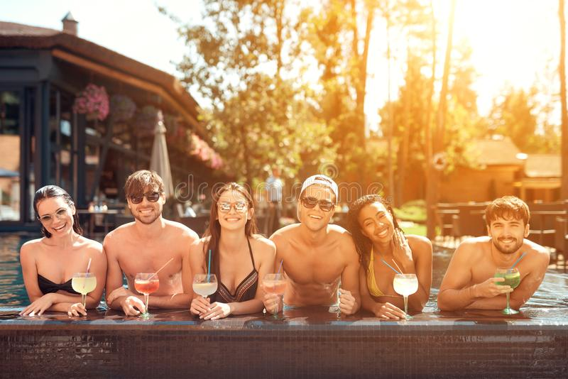 Company of happy friends drinks cocktail drinks in pool at summertime. Swimming pool party. royalty free stock images