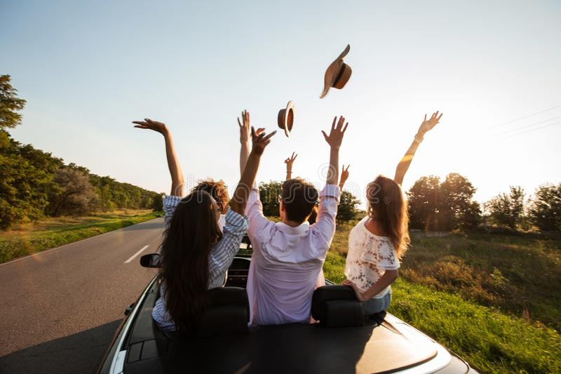 Company of happy young girls and guys sit in a black convertible car road and throw up their hats at sunset royalty free stock images
