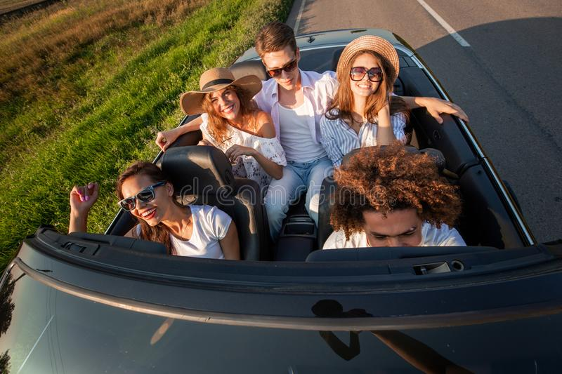 Company of happy young girls and guys are sitting in a black convertible car road on a sunny day. Top view.  stock image