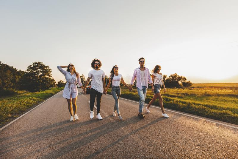 Company of happy young stylish guys walk on a country road on a sunny day stock image
