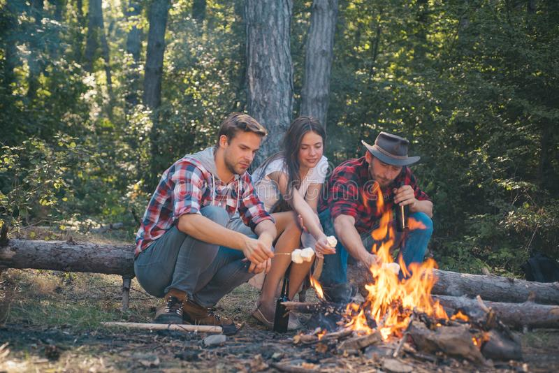 Company having hike picnic nature background. Friends roasting hotdogs on sticks at bonfire and having fun at camp fire royalty free stock photos