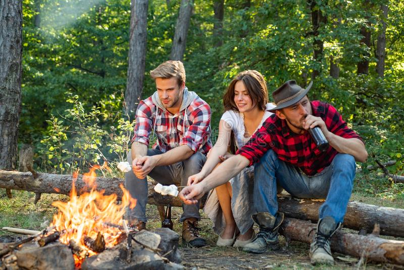 Company having hike picnic nature background. Weekend. Happy young people camping in woods. Hikers sharing impression of stock photo