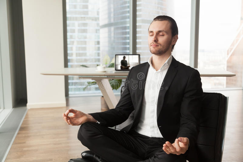 Company leader practices yoga during break at work. Businessman meditates in lotus position on coach in modern office. Company leader practicing yoga during royalty free stock photo