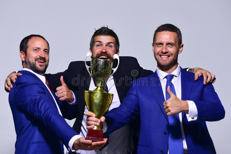 Company leaders hold golden prize, show thumbs up and hug. Partners celebrate winning competition. Business victory and support concept. Company leaders hold stock photography