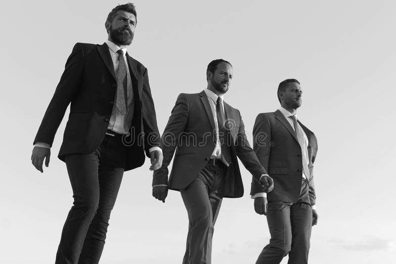Company leaders make step to success on blue sky background. Business success and cooperation concept. Businessmen with. Confident faces in formal suits and royalty free stock photo