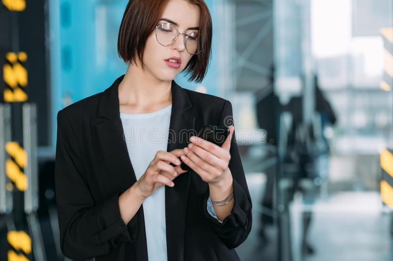 Company leadership arrogant beauty business woman. Company leadership. Arrogant beauty. Self assured business woman checking mobile stock photography
