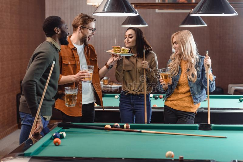 Company of multiethnic friends eating and drinking beside pool table. At bar royalty free stock images