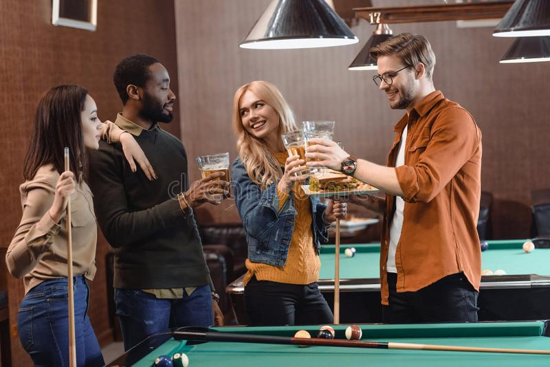 Company of multiethnic friends eating and drinking beside pool table. At bar royalty free stock photography